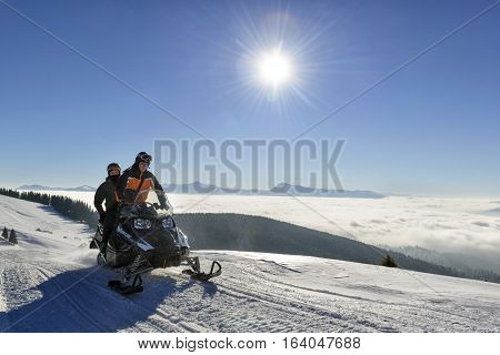 People driving snowmobile for a ride high in the mountains Bukovel ski resort Ukraine December 2016.