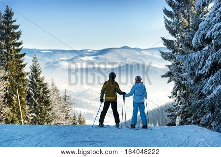 Man and woman skiers keeping hands and enjoying beautiful mountain landscape on a winter resort