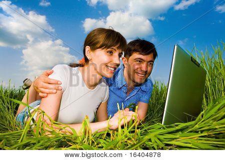 休闲快乐的夫妻在户外的便携式计算机上。躺在绿色的草地上。