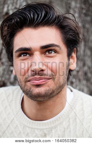 Happiness and joy. A young and handsome man with expression of happiness, joy, contentment. Portrait close, face beautiful and attractive. Stylish hair and slight beard.