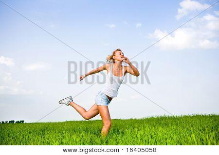 Happy girl is running in a field