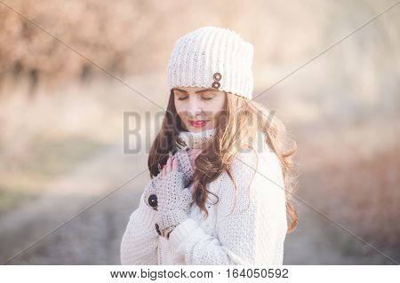 Winter portrait of a beautiful young woman in the sunny light