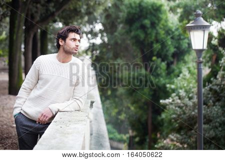 Dreamy young handsome man waiting for the first meeting. Latin lover. A beautiful and young Italian boy is leaning on a wall outdoors in a park. He looks at a lamppost in the town.He is waiting for his girlfriend? Concept of love, waiting, passion.