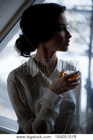 Young woman with glass of whiskey at background of window. She stands with glass in her hand and looking thoughtfully into window.