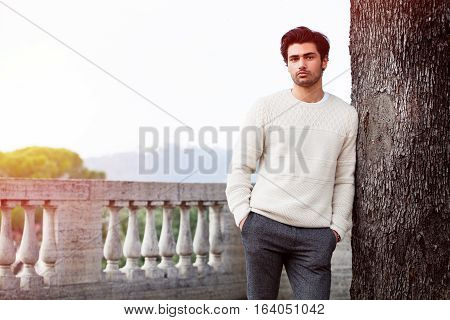 Attractive young man model leaning against the tree. Fashion style. Beautiful young guy with hands in his pocket leaning against a tree in the center of Rome. Relaxed and serene attitude. Concept of beauty, fashion, relaxation and leisure.