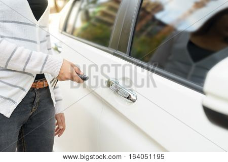 Asian young woman presses unlock button on remote control car key for opening car door