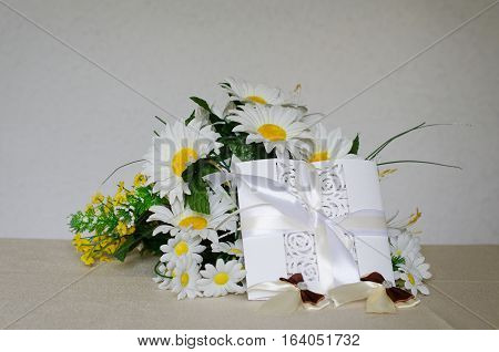 White openwork card with satin ribbon a bouquet of daisies on a white background