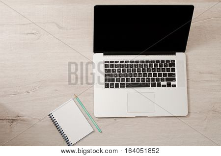 Top view of a laptop and a notebook with a pencil on a light wooden background space for text