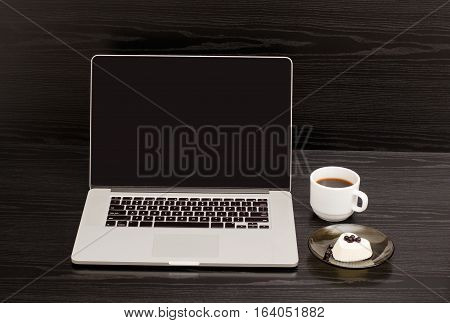 Open the laptop mug of coffee and panna cotta on black wooden table a lunch break