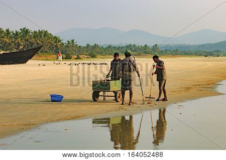 Goa, India - November 23, 2012: A team of workers begin clearing the Cavelossim Beach from plastic bottles and other trash South Goa India.