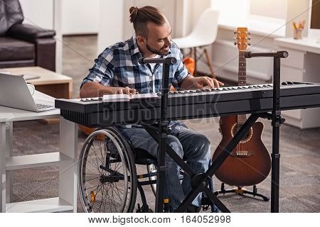 This would sound great. Committed handsome disabled guy having good time writing and recording music during his leisure time while sitting in a wheelchair in his living room