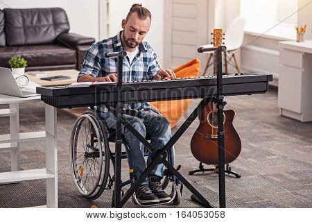 I can practice everywhere. Attractive dedicated handicapped man playing piano and making a record while spending time in his living room and enjoying his hobby