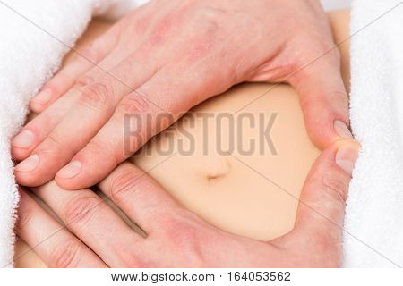 Male Hands In A Heart Shape On The Abdomen Of A Pregnant Woman Close-up