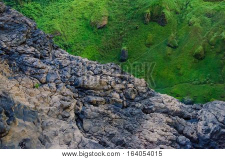 Stark contrast between green moss and grass and brown rock cliff deep in rain forest of Cameroon, Africa.