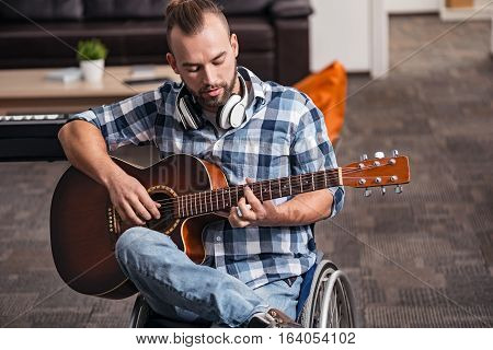 Caught in the moment. Gifted young disabled man totally diving into the process of songwriting during his free time while sitting in his living room