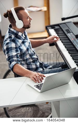 Feeling the vibe. Brilliant concentrated disabled musician editing recently recorded material creating a new song while sitting at the piano and using his laptop