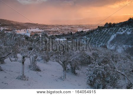 Enchanted atmosphere at winter sunset over Foligno with snow