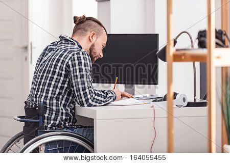 Putting down the essentials. Stylish dedicated disabled guy sitting at his desk at home and writing something down while planning his tasks for a day