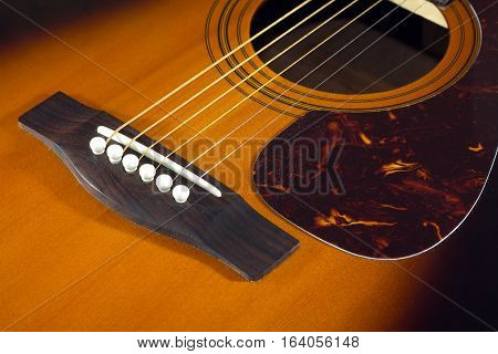 Classic acoustic guitar sunburst color top fragment with six strings closeup