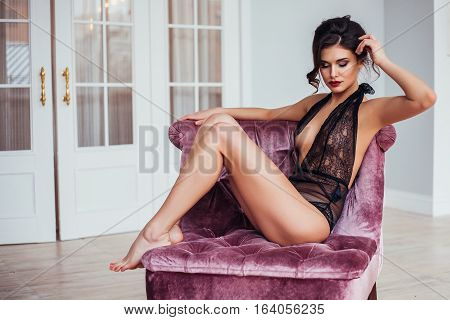 Young Beautiful sexy woman with perfect skin, professional make-up and hairstyle posing in bedroom, wearing seductive lingerie.