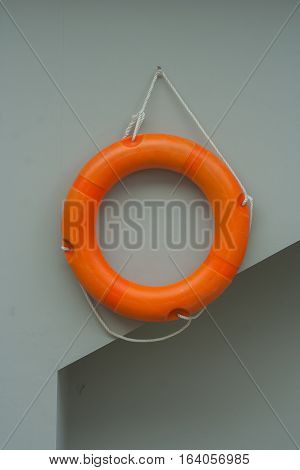 Orange life ring with white rope hanging on gray wall near swimming pool