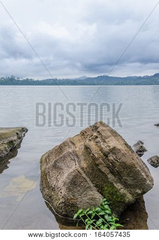 Large rock laying in peaceful Barombi Mbo crater lake in Cameroon, Africa.