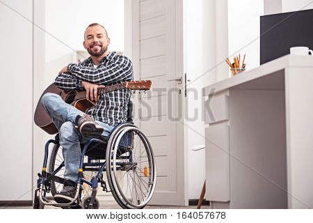 Enjoying every moment of it. Attractive smiling young man looking delighted while posing for a photographer and sitting on a wheelchair in his apartment