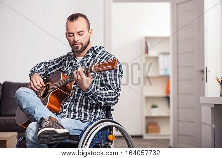 Magic of the sound. Focused talented young musician sharing a creative moment while playing new melody and spending his free time at home in a bright living room