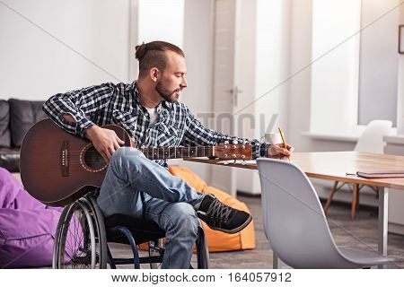 Brilliant ideas. Devoted talented young gentleman improving the quality of his new composition by writing lyrics down while enjoying his hobby in a living room