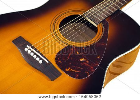 Classic acoustic guitar sunburst color top fragment with six strings isolated on white closeup