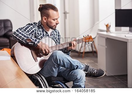 Unusual is better. Creative talented young musician making new bold decisions on his new track while trying them out on his guitar spending free time doing what he likes