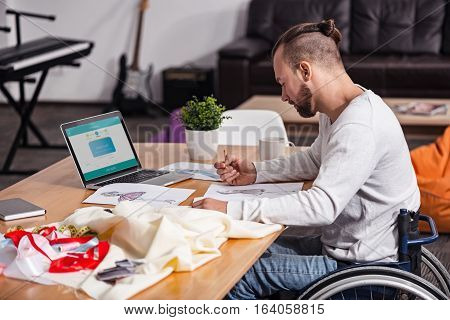 Expressing ideas on paper. Focused devoted disabled man developing a number of designs for his new dress while working home sitting at the table in bright living room