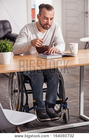 Nurturing body and mind. Handsome intelligent interested man having breakfast and reading an interesting book while sitting in a wheelchair at the table