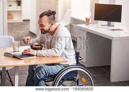 Positive start. Positive interested intelligent gentleman perusing an art book while eating cereal and having morning coffee at the table