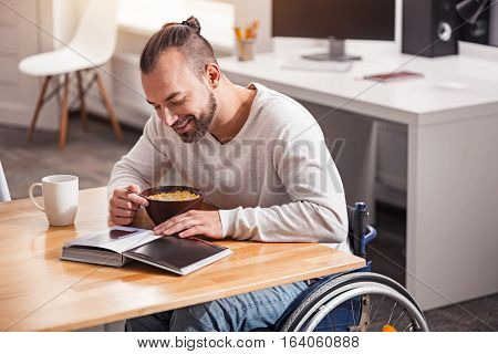Cannot leave it for a moment. Stylish positive smart man enjoying morning meal and coffee while casually looking through a book on his table