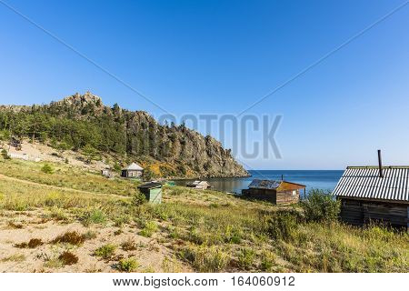 On the sandy shores in a small Bay on the lake is a small village of several wooden houses.
