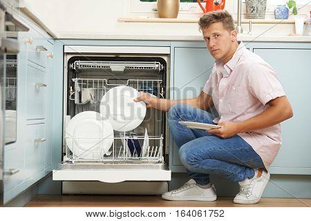 Portrait Of Bored Man Loading Dishwasher In Kitchen