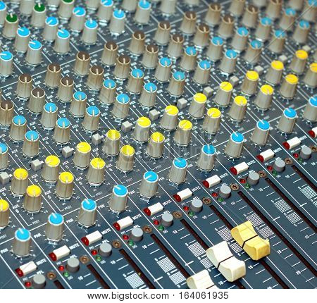 Big multichannel audio sound mixer with many buttons and knobs. Diagonal view closeup