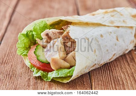 Döner kebab with tomatoes and greens on a wooden background