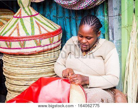 ADDIS ABEBA ETHIOPIA - JUNE 06 2016: Ethiopian woman makes Habesha baskets for sale on a local market in Addis Abeba.