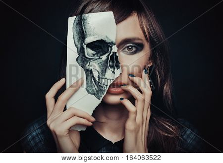 beautiful woman with a painted skull which covers half of the face the concept of cosmetics safety threat to life