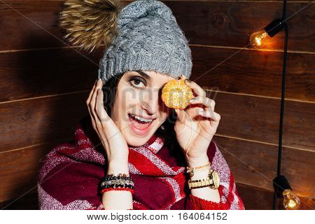 The Mood Of Winter. Young Beautiful Dark-haired Woman Smiling In  Clothes And Cap With Tangerines On