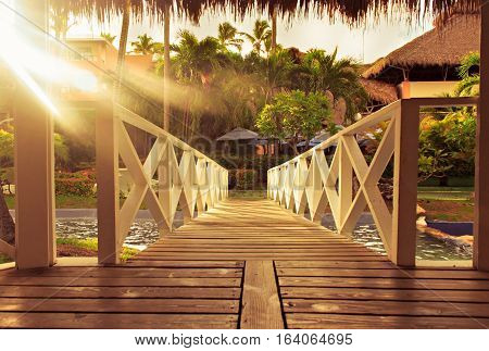 Wooden bridge with garden view and natural warm sun ray. Path to palms at sunrise. Tropical caribbean resort. Toned.