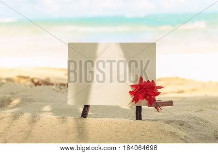 Empty paper card tropical flower decorated on beach, turquoise sea background. Soft focus. Retro bleached toned.
