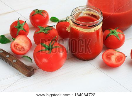 Bright red tomato juice in glass jar, fresh fruit scattered. Healthy low-calorie refreshing tasty drink.