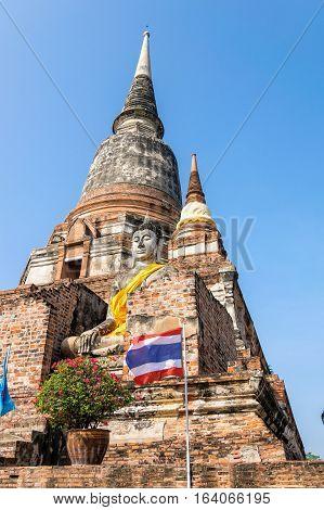Buddha statue at the bottom of a large ancient pagoda on blue sky background at Wat Yai Chai Mongkon temple in Phra Nakhon Si Ayutthaya Historical Park Ayutthaya Province Thailand