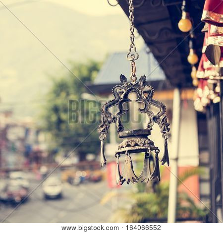 Dragon shapped candle holder hanging from a roof. Restraurant view on shoppinh street in Pokhara, Nepal.