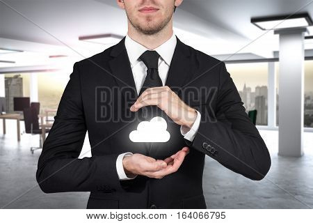 businessman in modern office protecting cloud symbol