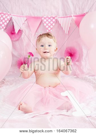 Portrait of cute adorable Caucasian baby girl with blue eyes in pink tutu skirt celebrating her first birthday with flower  and balloons looking in camera, cake smash first year concept