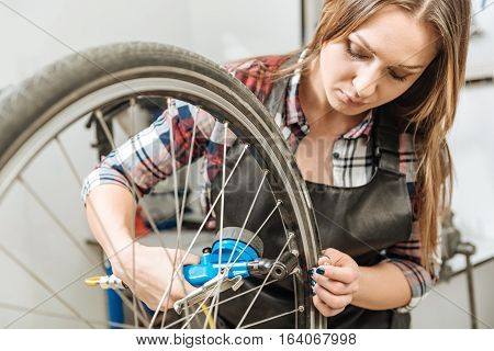 Using the tire gauge at work. Concentrated young skilled craftswoman standing in the repair shop and holding the wheel of the bicycle while measuring the pressure in tires